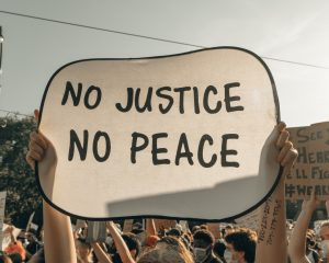 A picture of a crowd and a person holding a sign that reads No Justice No peace